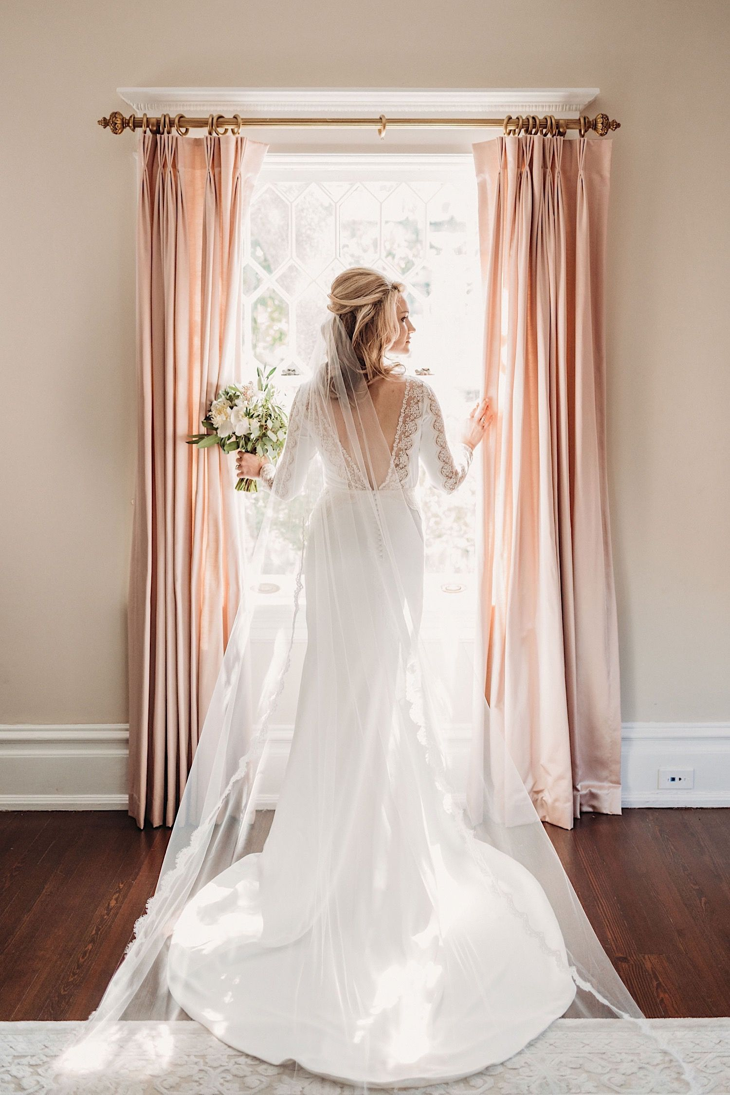 Bride in BHLDN wedding dress standing in the window