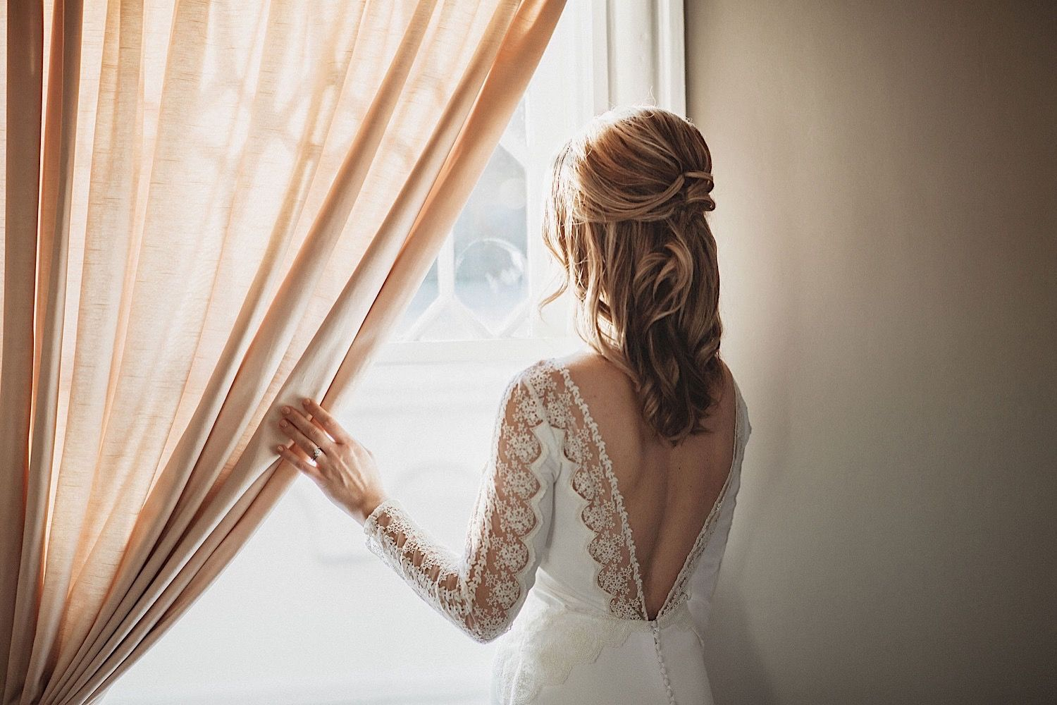 bride looking out the window holding onto a pink curtain
