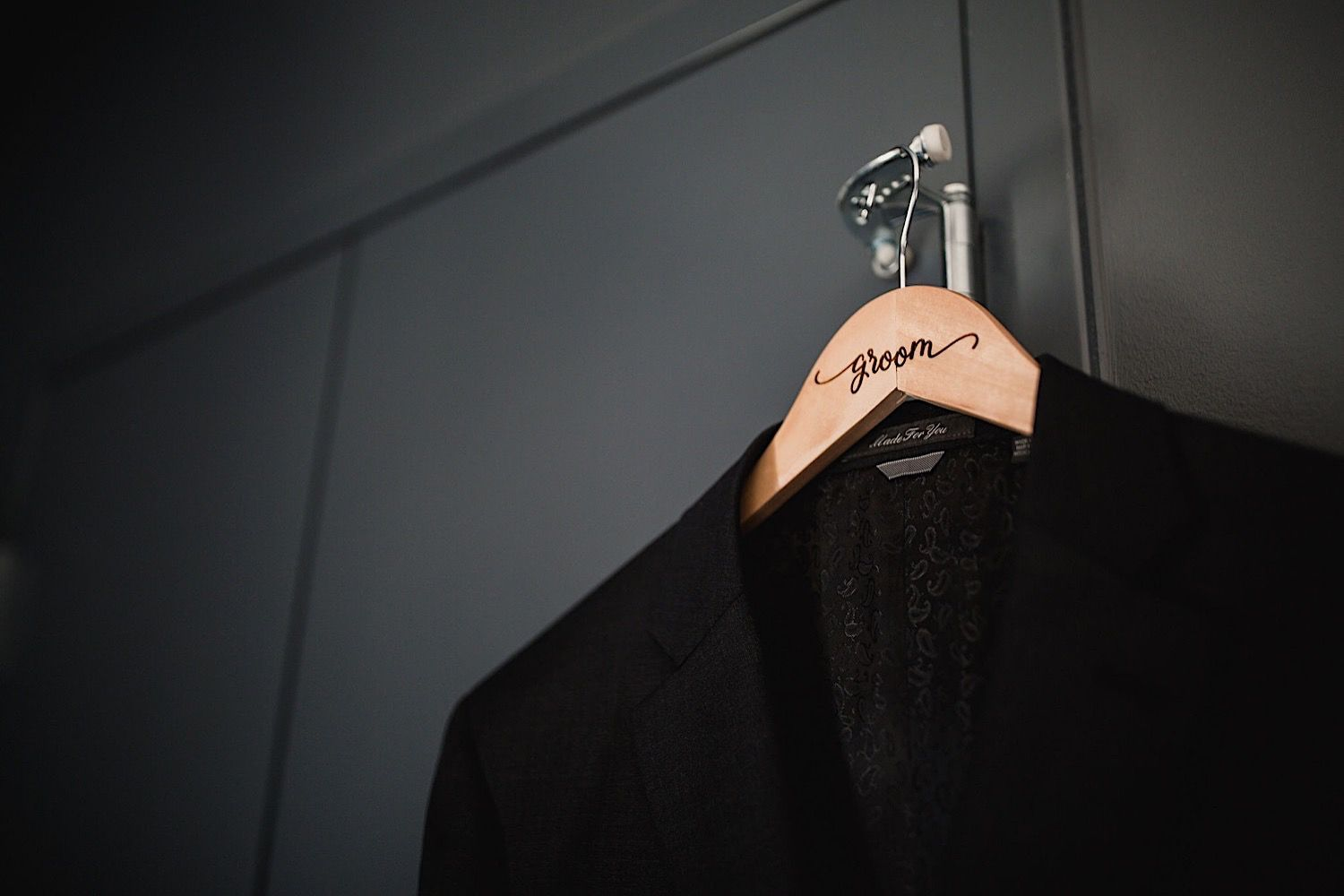 Suit jacket hanging on a hanger that says the groom