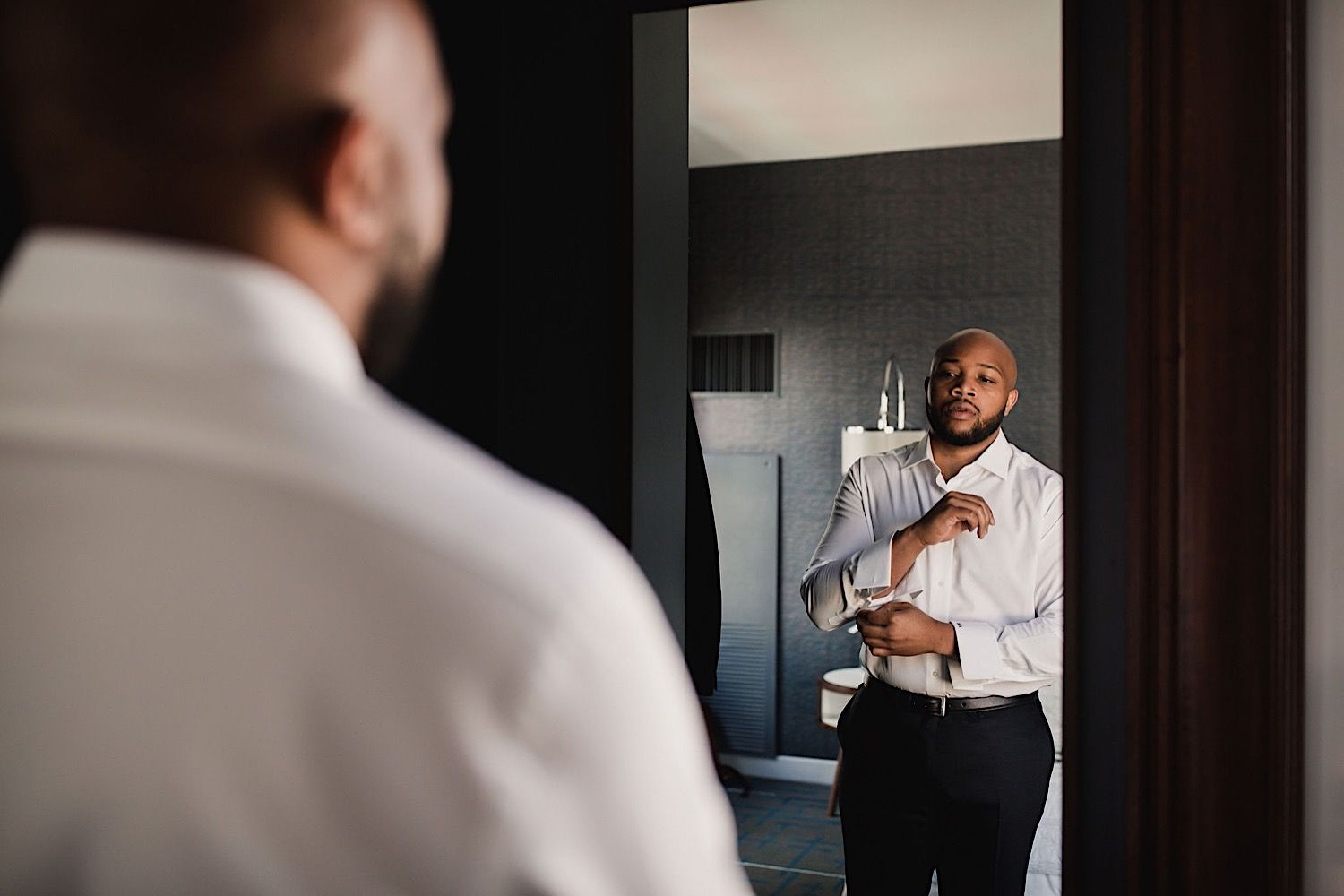 groom looking in the mirror at Le Meridien Hotel in Tampa as he gets dressed