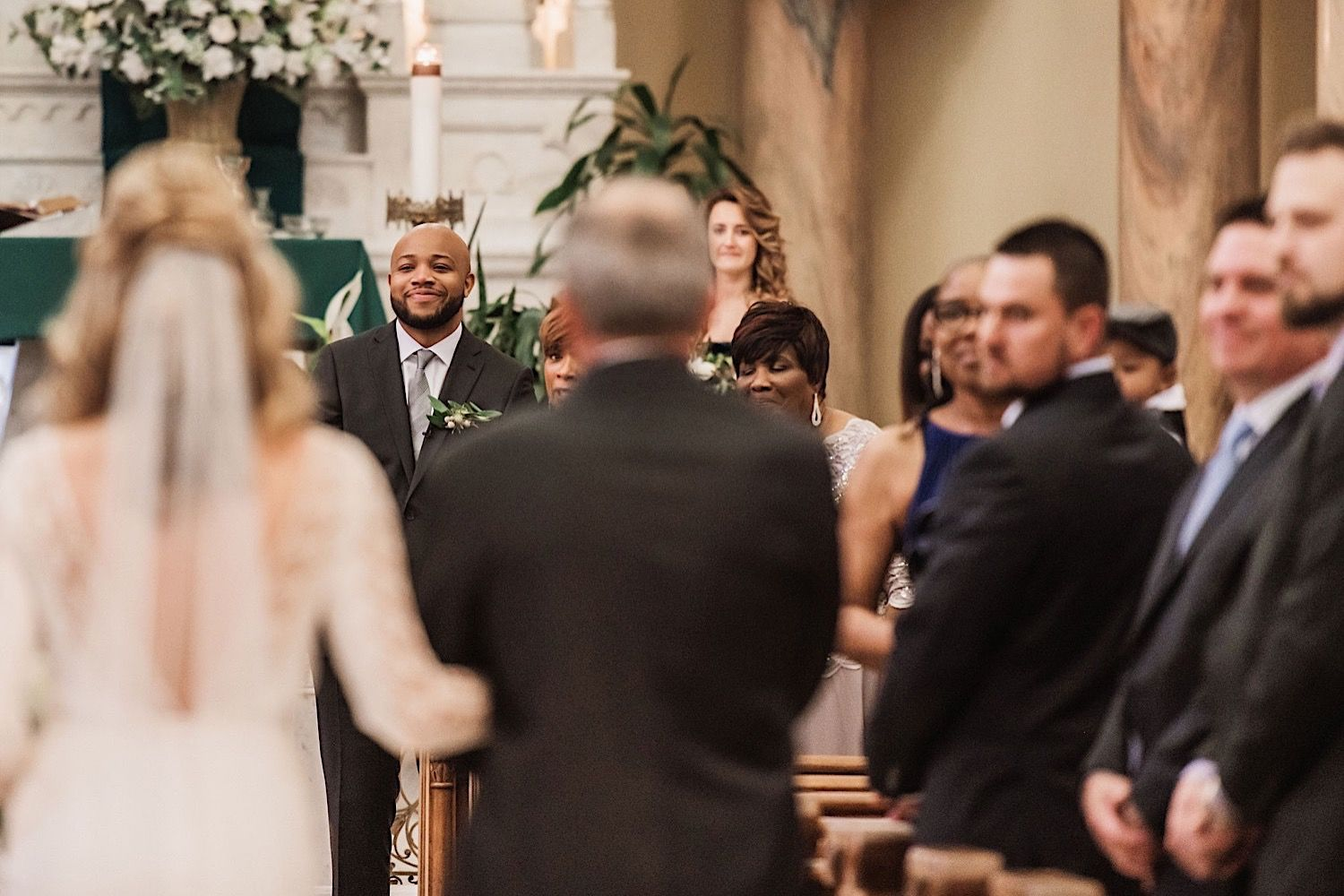 Groom seeing his bride for the first time as she walks down the aisle