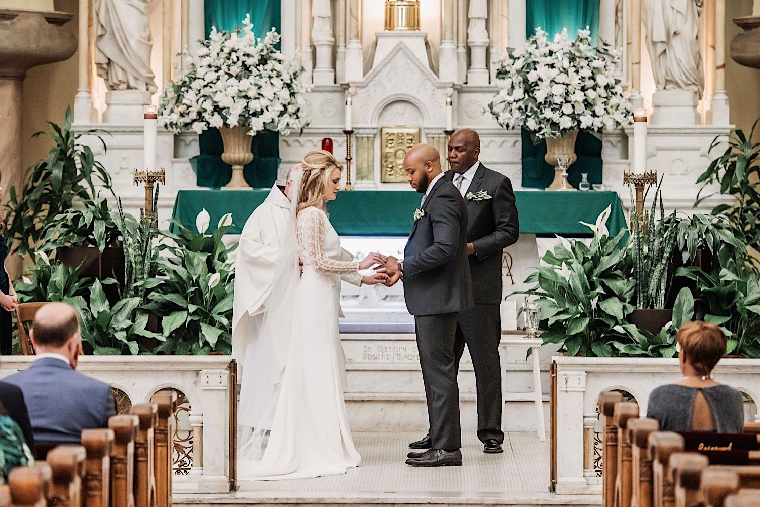bride and groom exchanging rings at the altar at sacred heart church