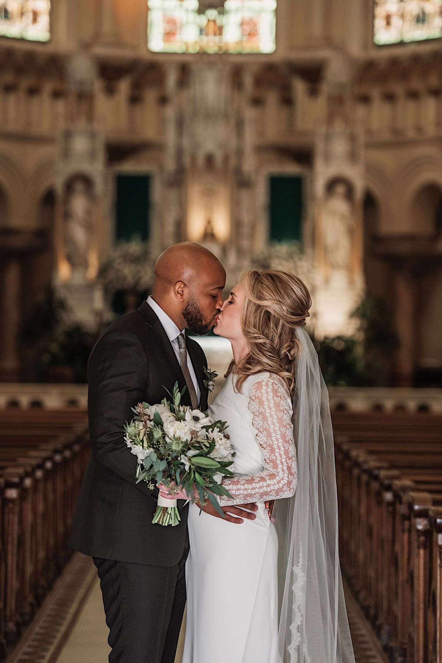 bride and groom standing in sacred heart church and kissing