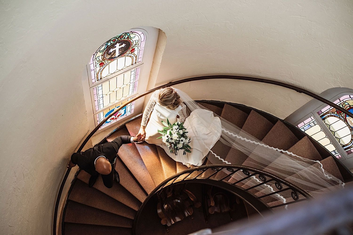 bride and groom walking down the stairs at sacred heart church