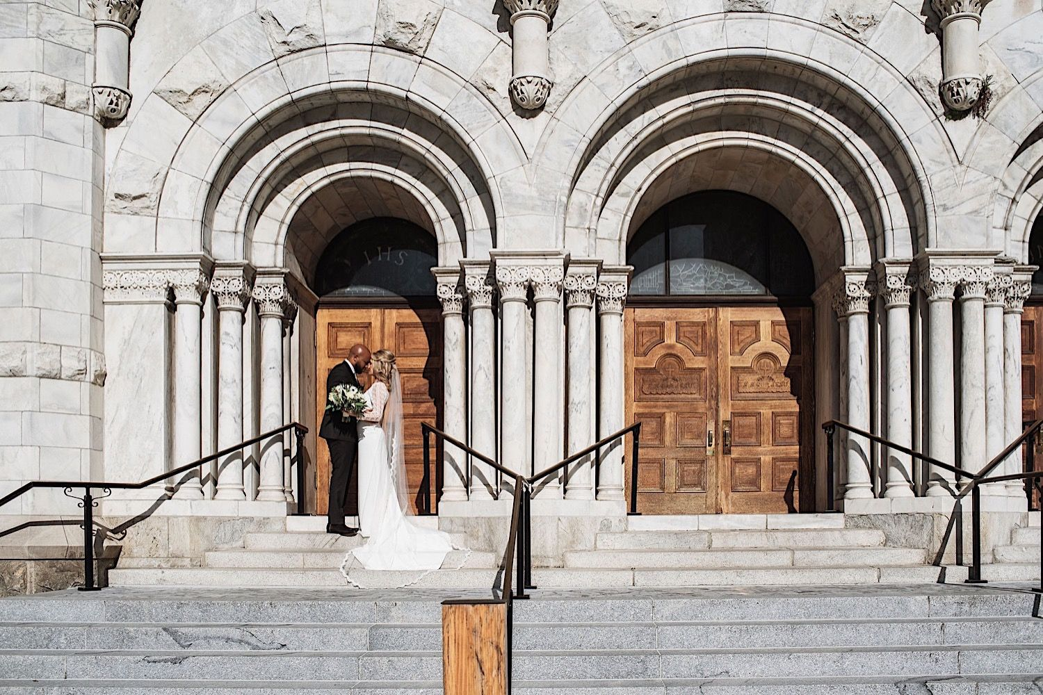 bride and groom standing in front of arched doorway on the steps of sacred heart church in downtown tampa