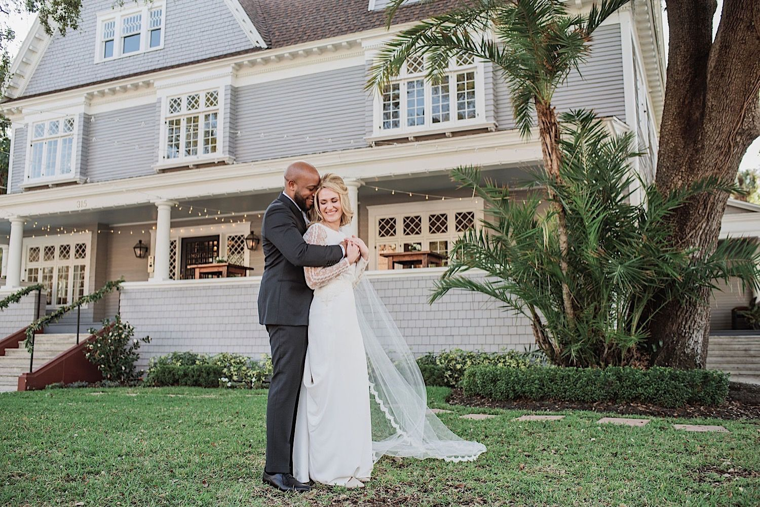 groom hugging bride in the front yard of the oral wedding venue