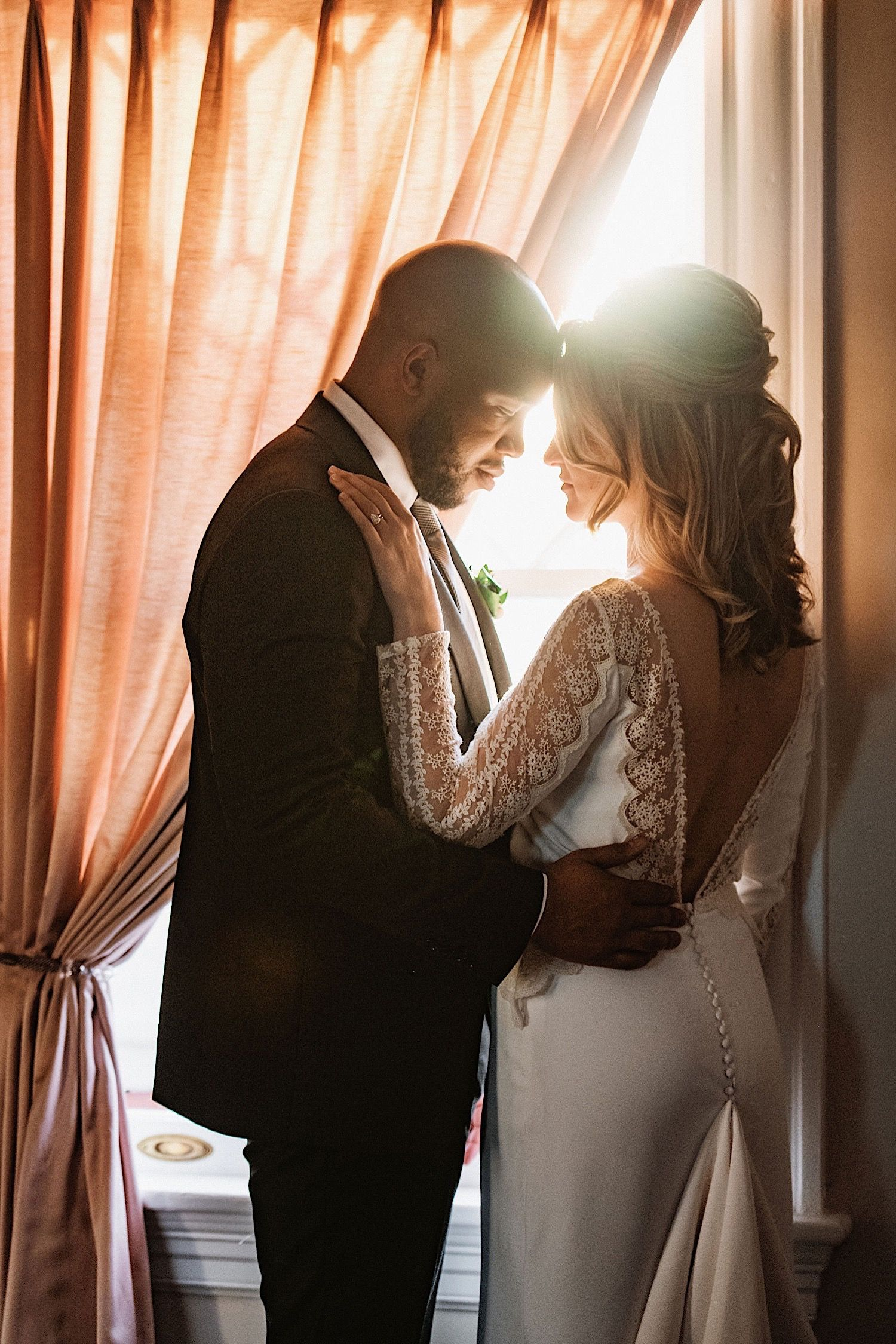 bride and groom touching foreheads in front of window with pink curtain at the orlo