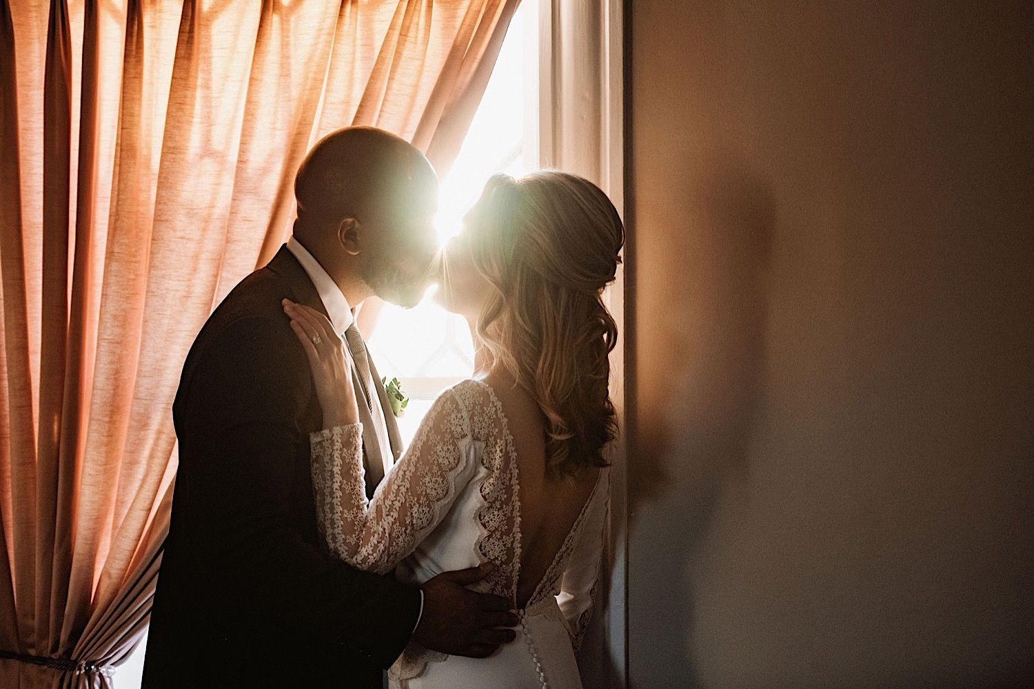bride and groom kissing in front of a window with sunlight shining thorugh