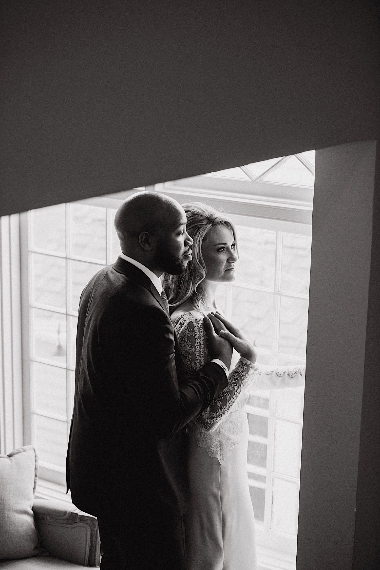 bride and groom looking out the window together