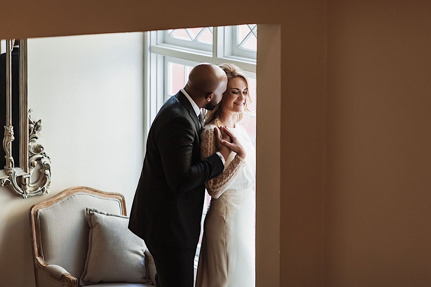 groom hugging bride from the back near the window at the orlo