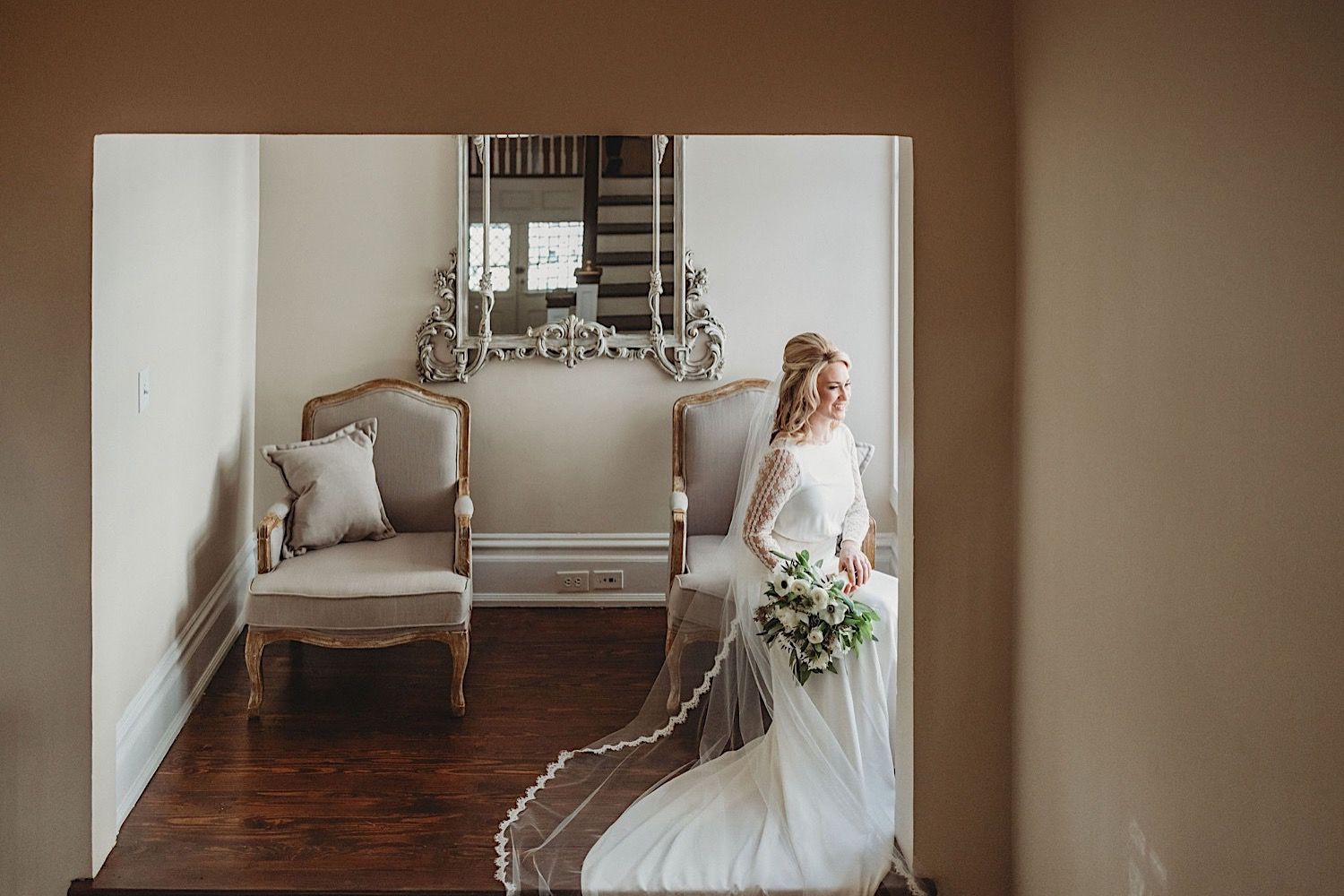 bride sitting in chair holding bouquet and looking out the window