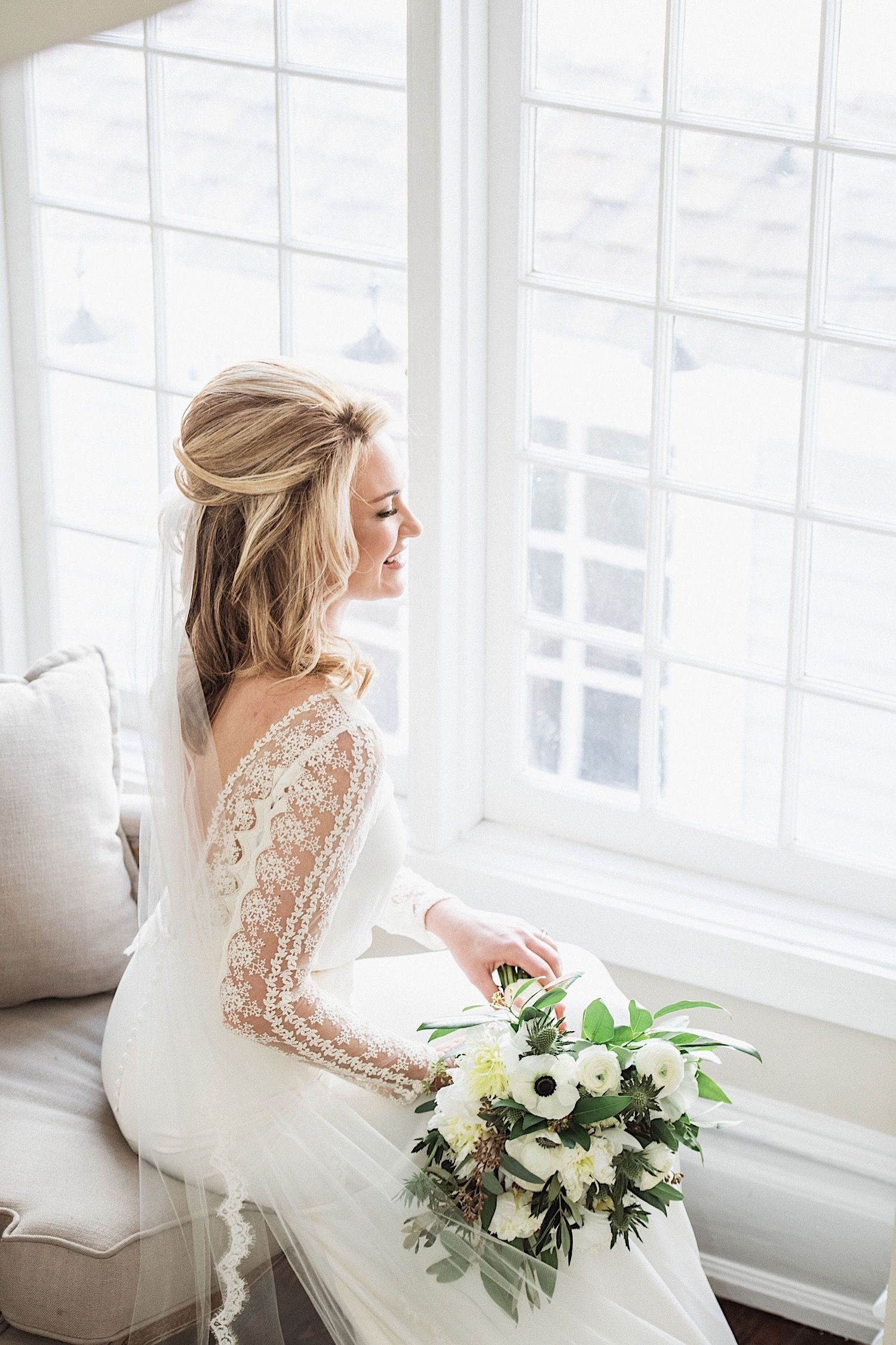 bride looking out the window while holding bouquet and wearing a BHLDN gown