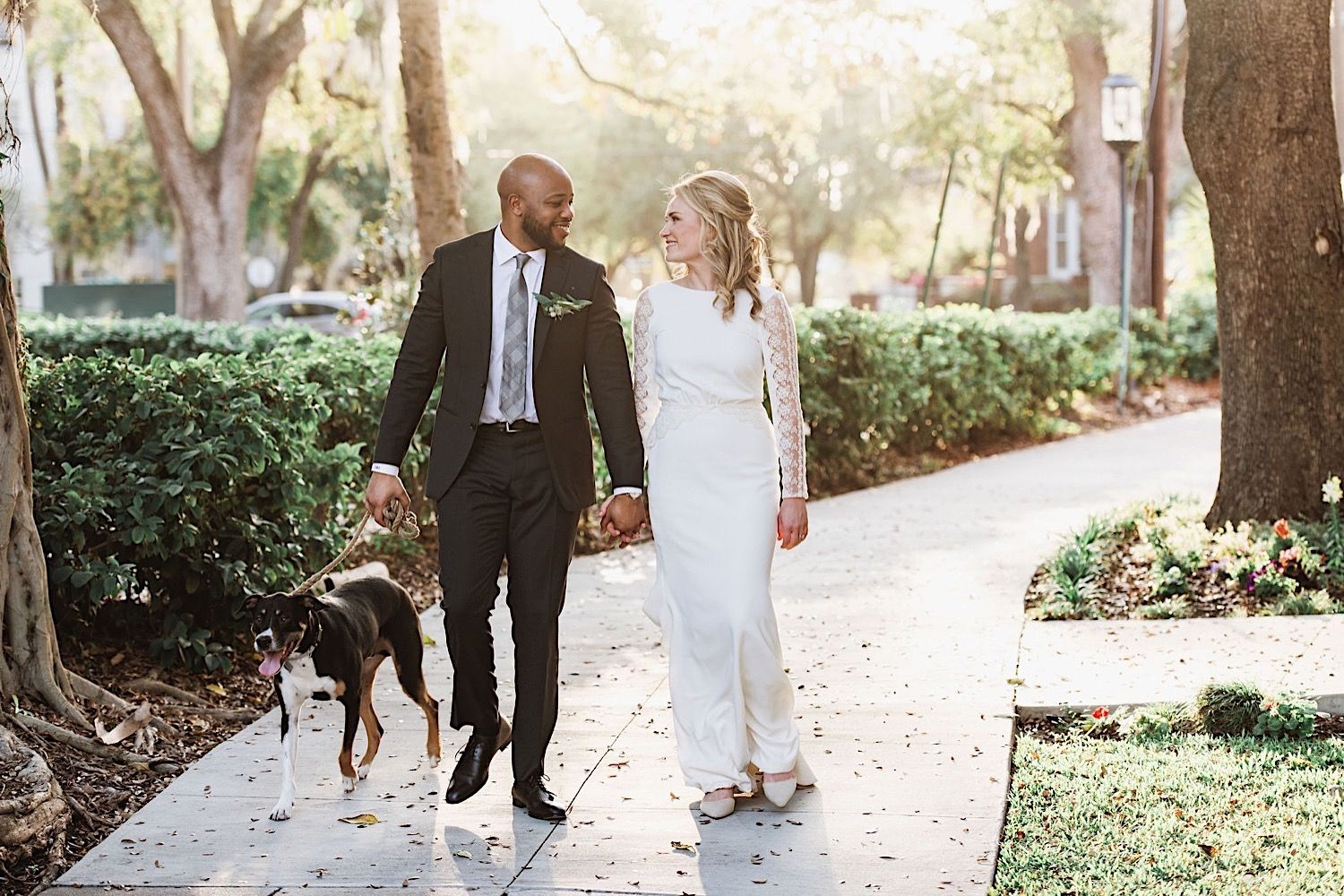 bride and groom walking their dog