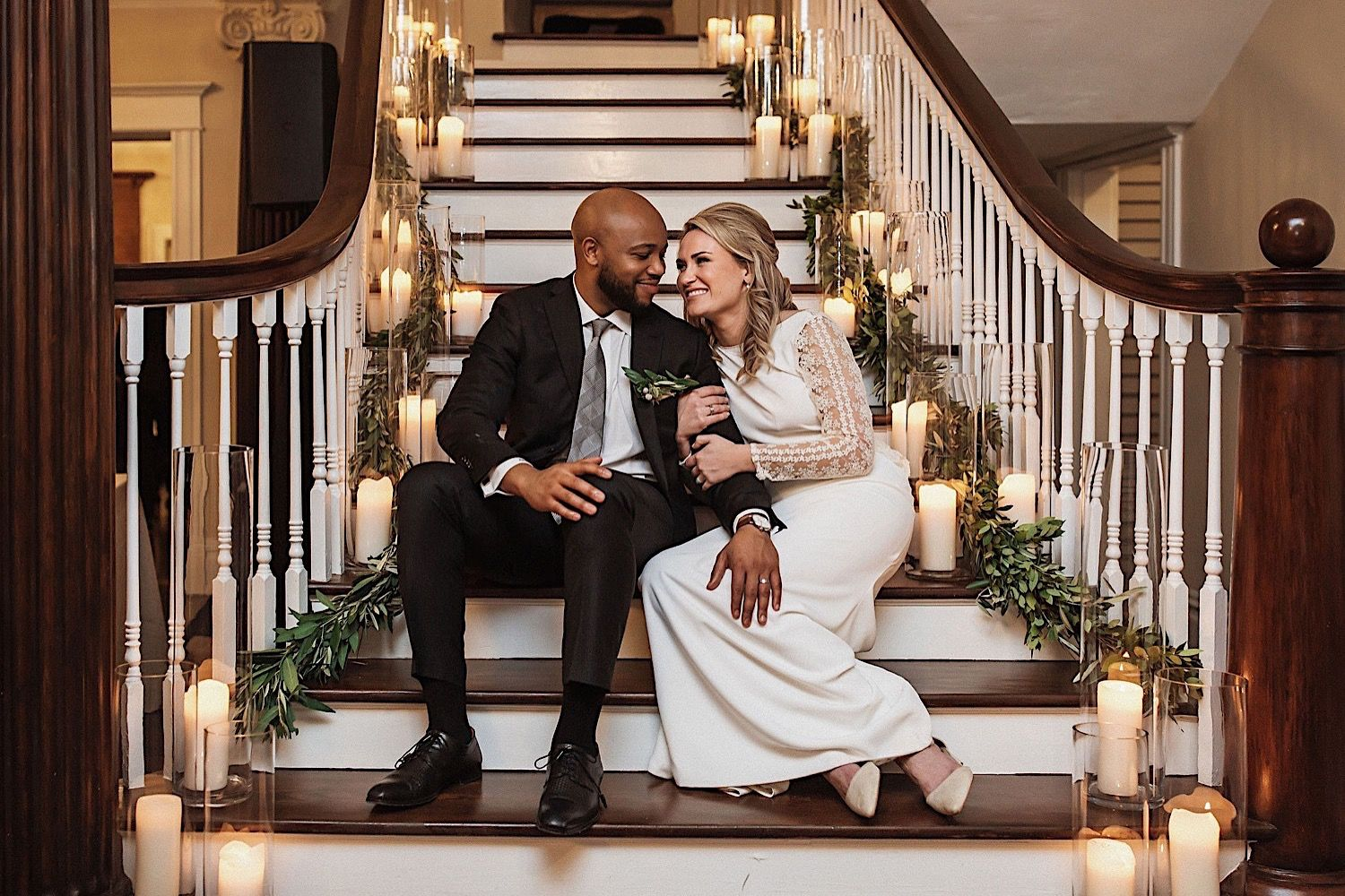 bride and groom sitting on the stairs with candles and greenery at the Orlo in tampa