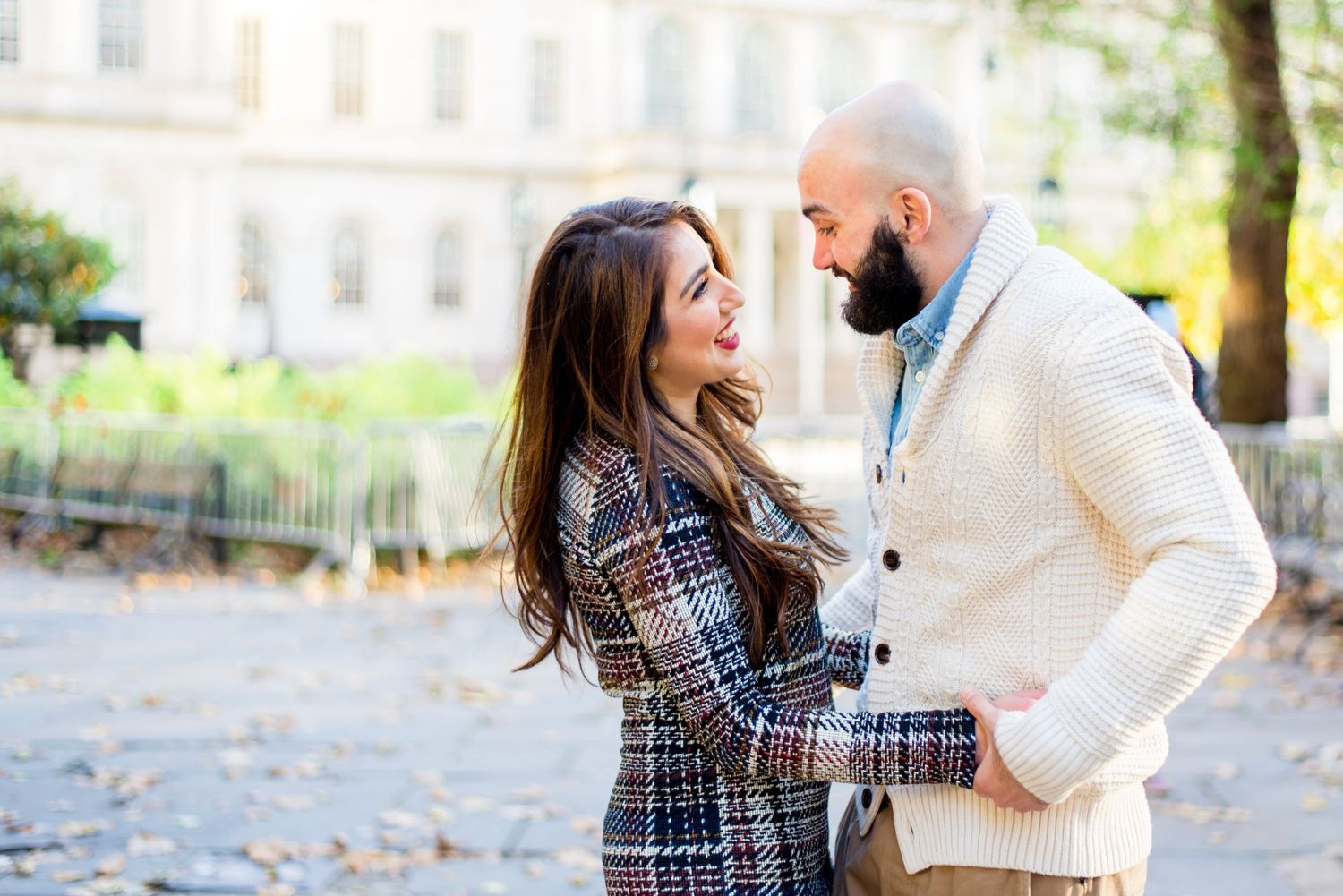 young engaged couple in fall clothes hold hands and smile at each other for NYC City Hall Engagement Pictures