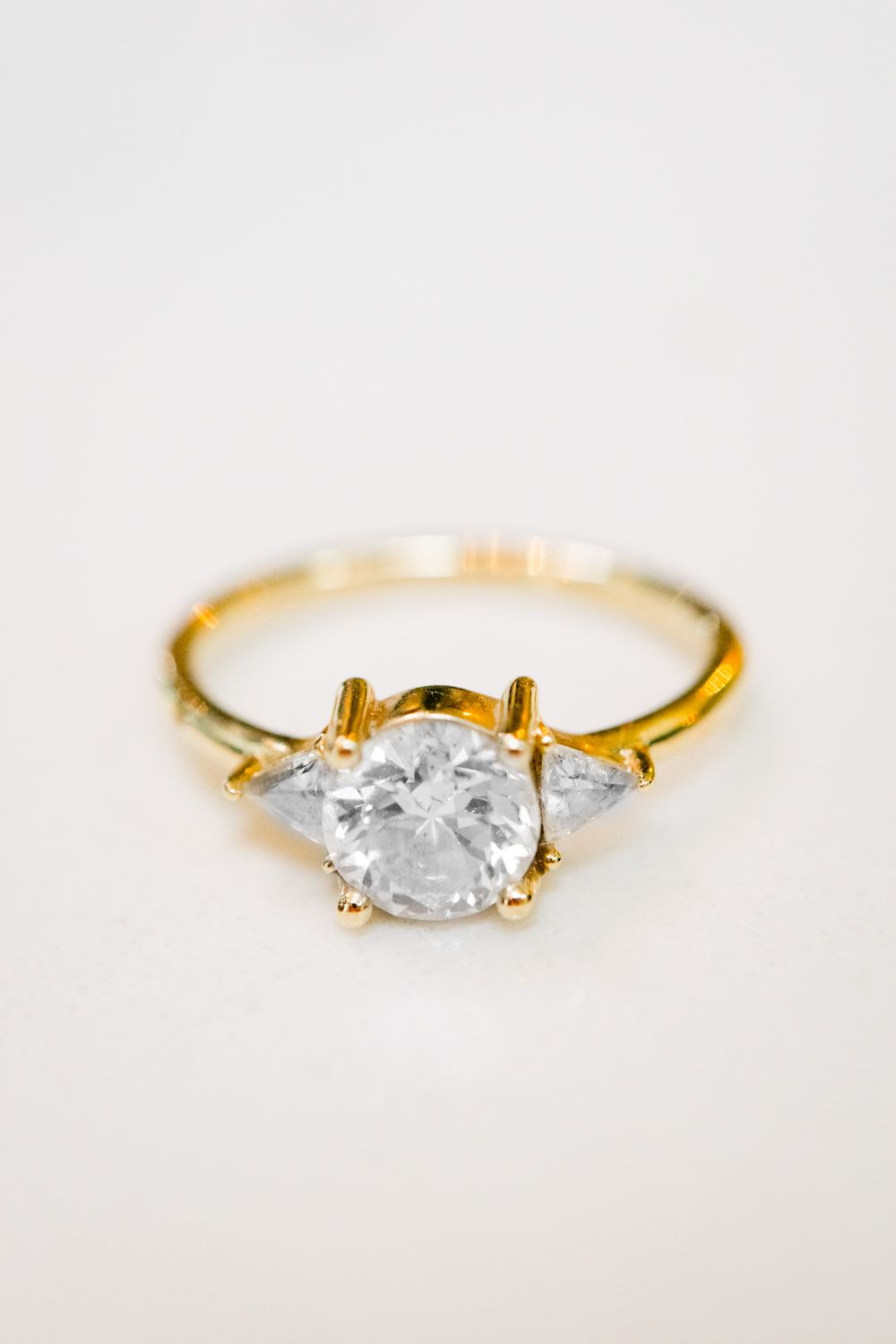 gold band engagement ring with round diamond and two triangle side stone diamonds