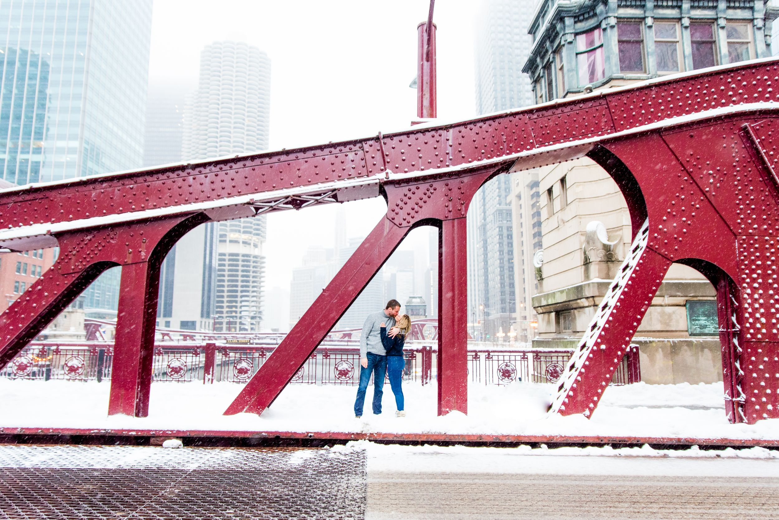 engaged couple in Chicago standing under bridge kissing in the snow