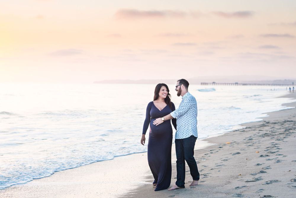 Pregnant mother and husband on the beach in San Clemente, CA
