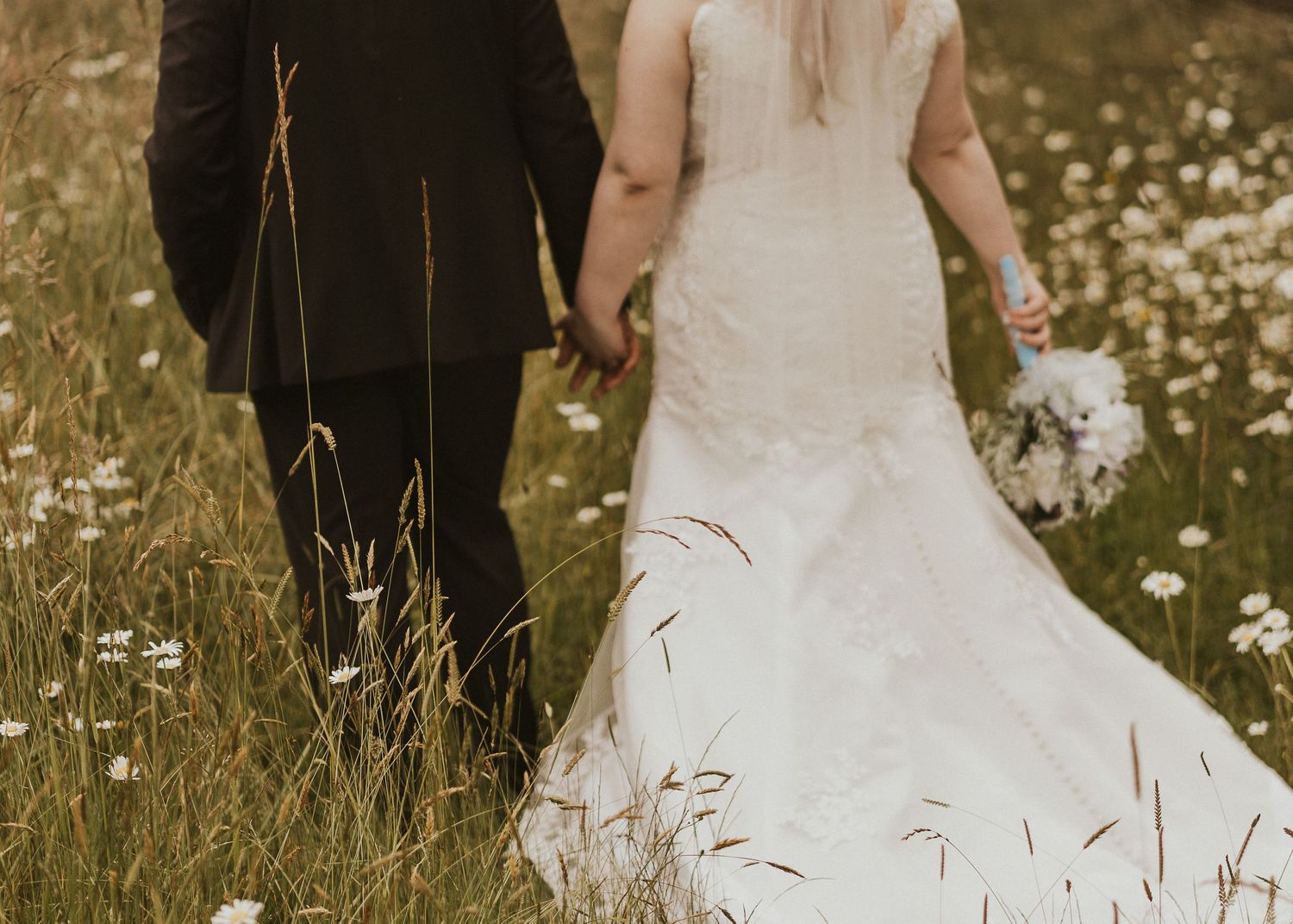 Newly married couple walks hand in hand through a field of daisys