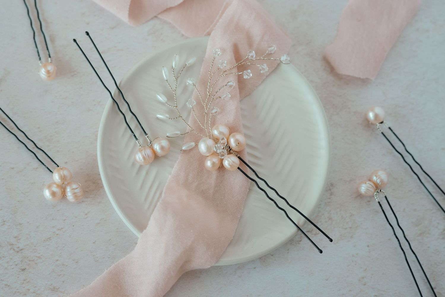 Pink hair pins on cream plate with pink ribbon