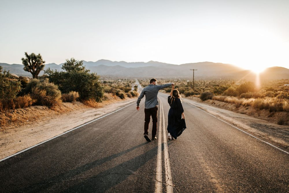 couple walking down a road at joshua tree