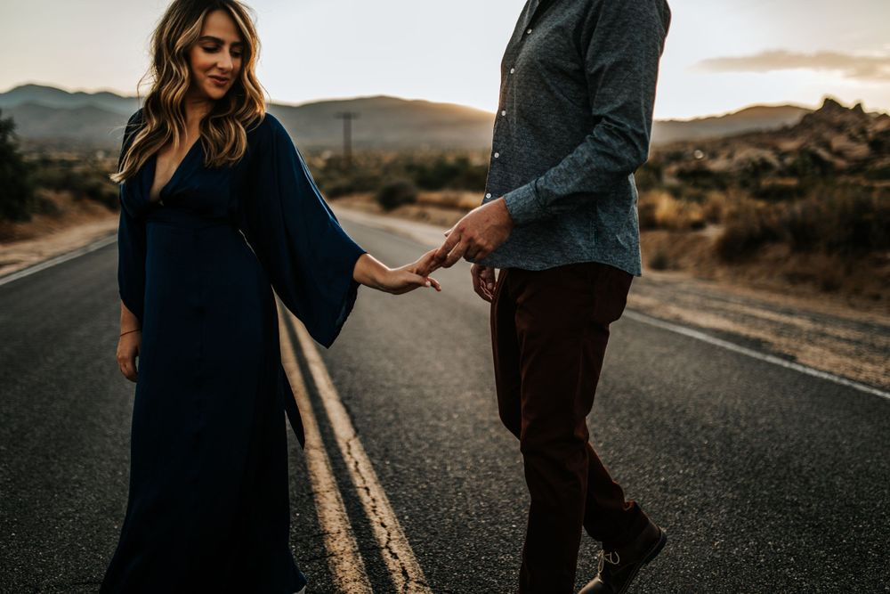 couple holding hands on road