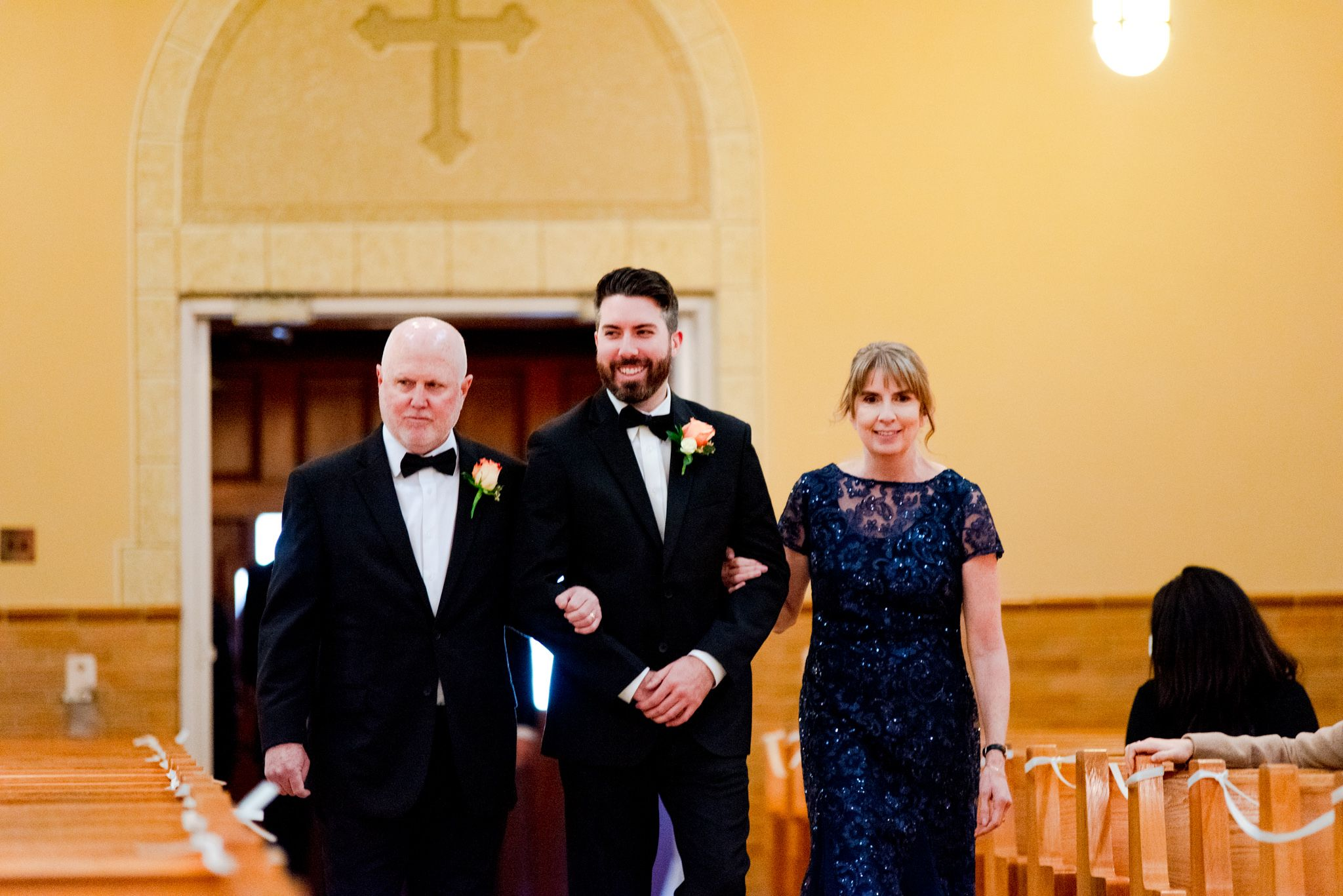 groom walking down the aisle with dad on let and mom on right in blue sparkly dress