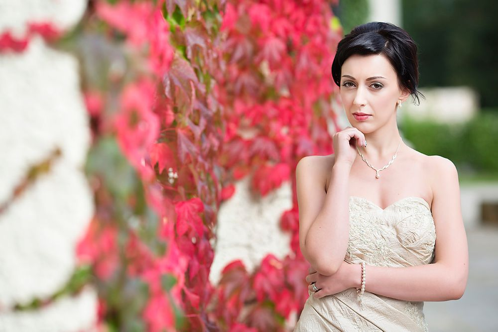 Beautiful dark haired bride outdoors in her Victorian wedding dress posing next to red foliage at Mitton Hall