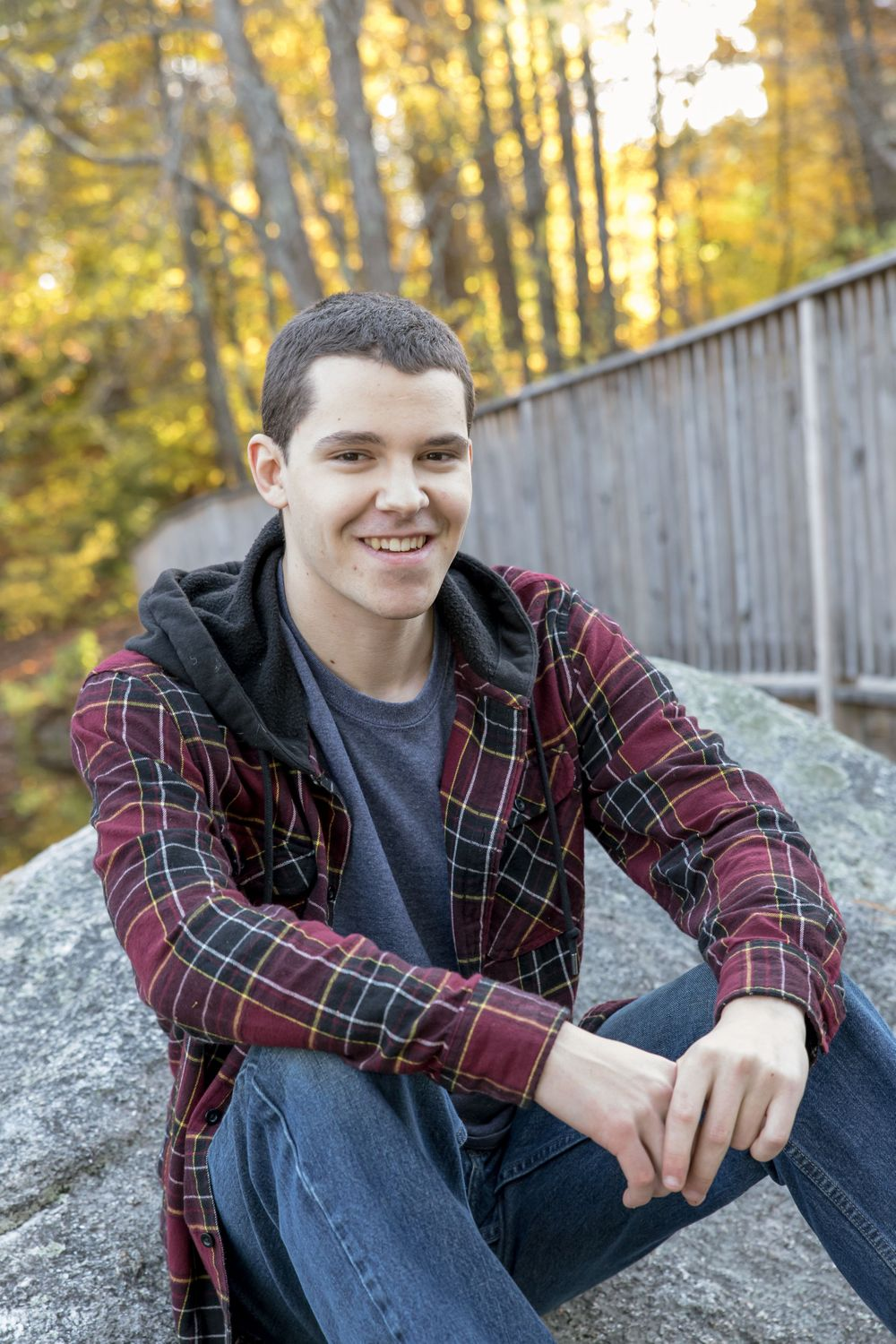young mans senior portrait  sitting on a foot bridge red plaid shirt jeans  Barnstead NH.
