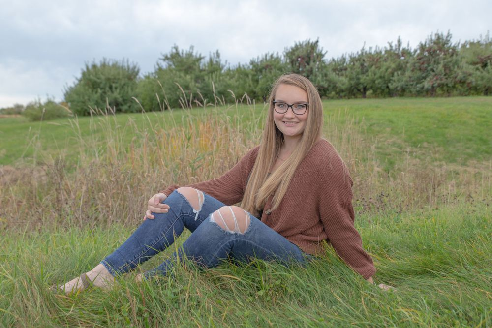 Pittsfield Middle High School senior pictures outside  in the field. brown sweater with holey jeans.