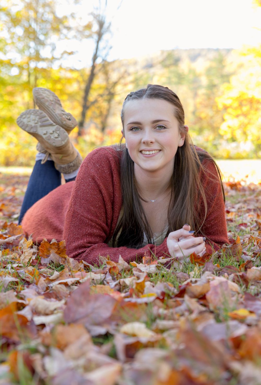 young women's Photography session laying on freshly fallen leaves with yellow trees in back.New Durham NH.