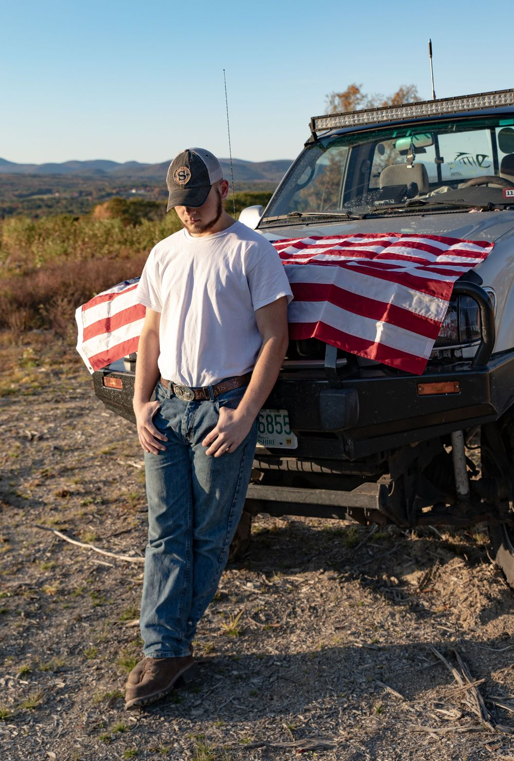 young mans senior portrait with a american flag covered truck whit tee jeans  Barnstead NH.