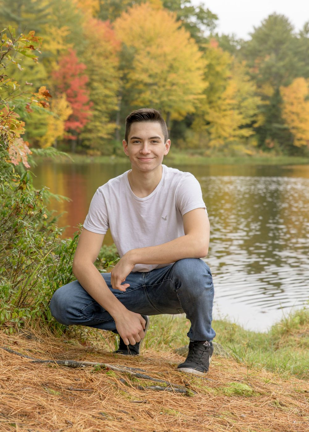 senior photography fall color young man white tee and jeans squatting down in front of a pond Rochester NH