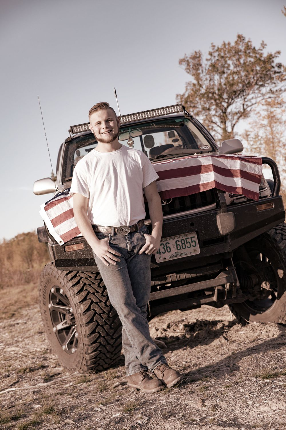 High school boy with his american flag covered truck whit tee jeans  Barnstead NH.