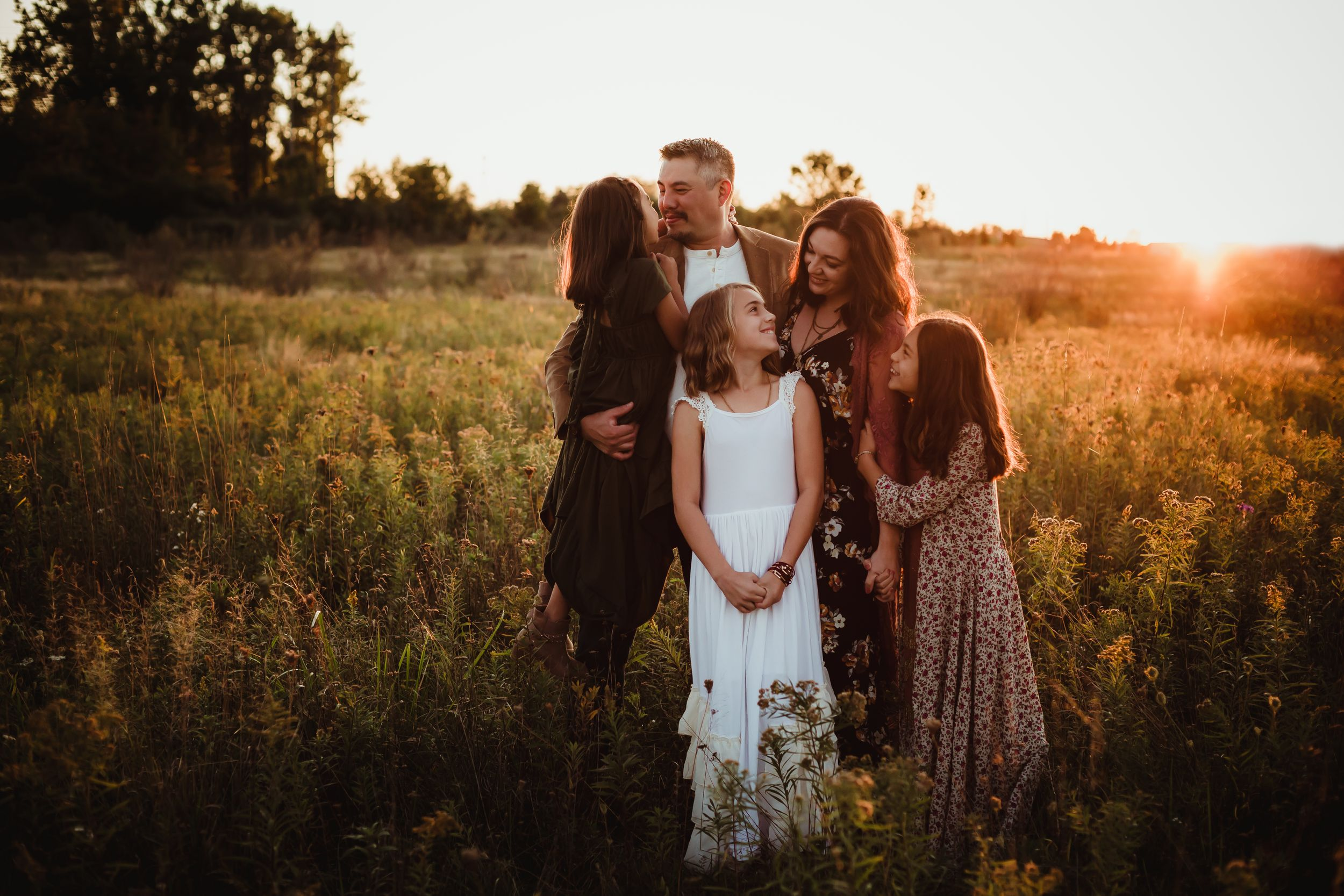 Father, mother, and three daughters embracing and smiling at each other in a field with a golden sunset behind them.