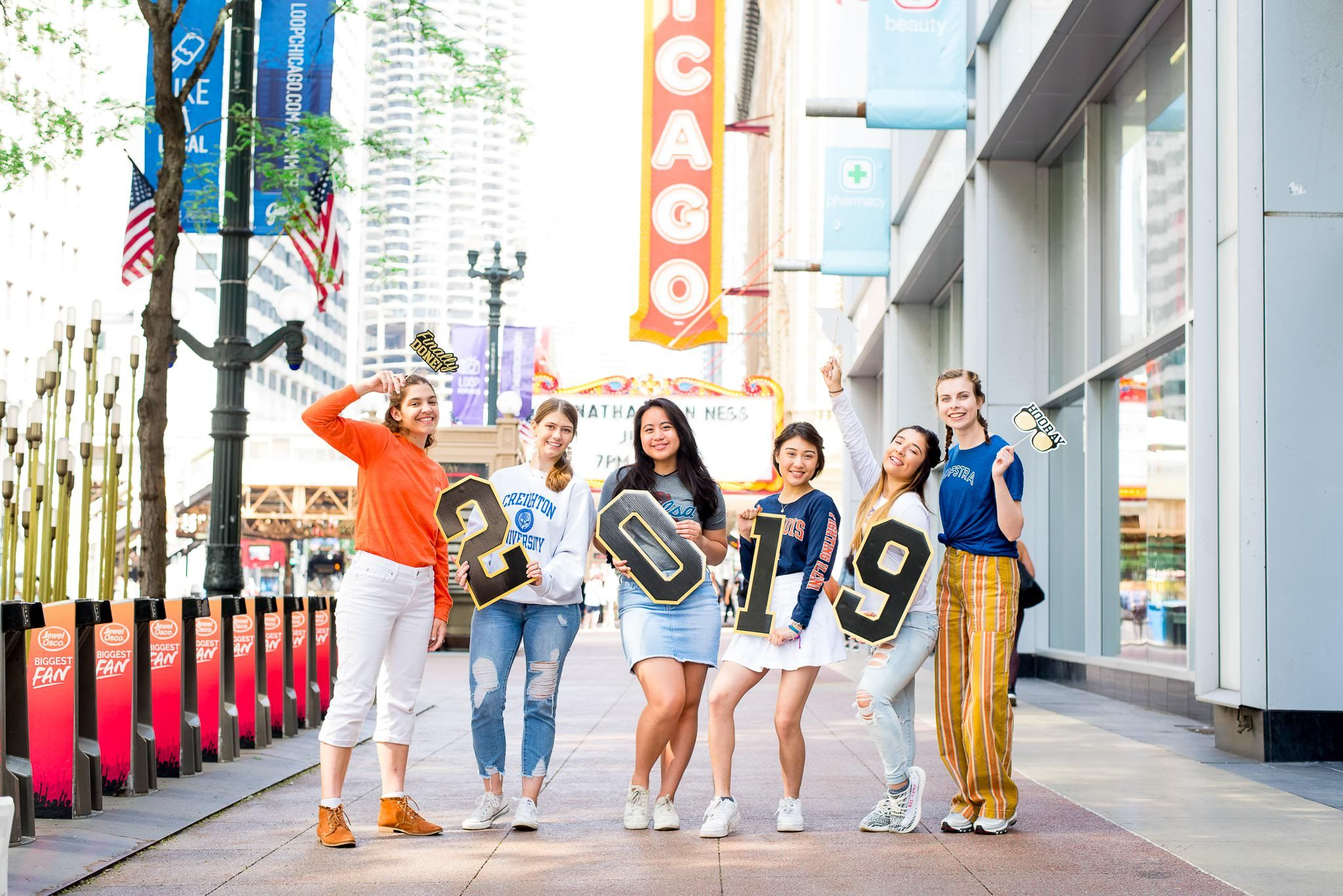 six senior girls in front of the Chicago Theater sign for Chicago senior pictures holding up 2019