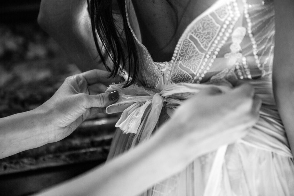rebecca skidgel photography mesa arizona wedding bride getting ready with maid of honor tying dress