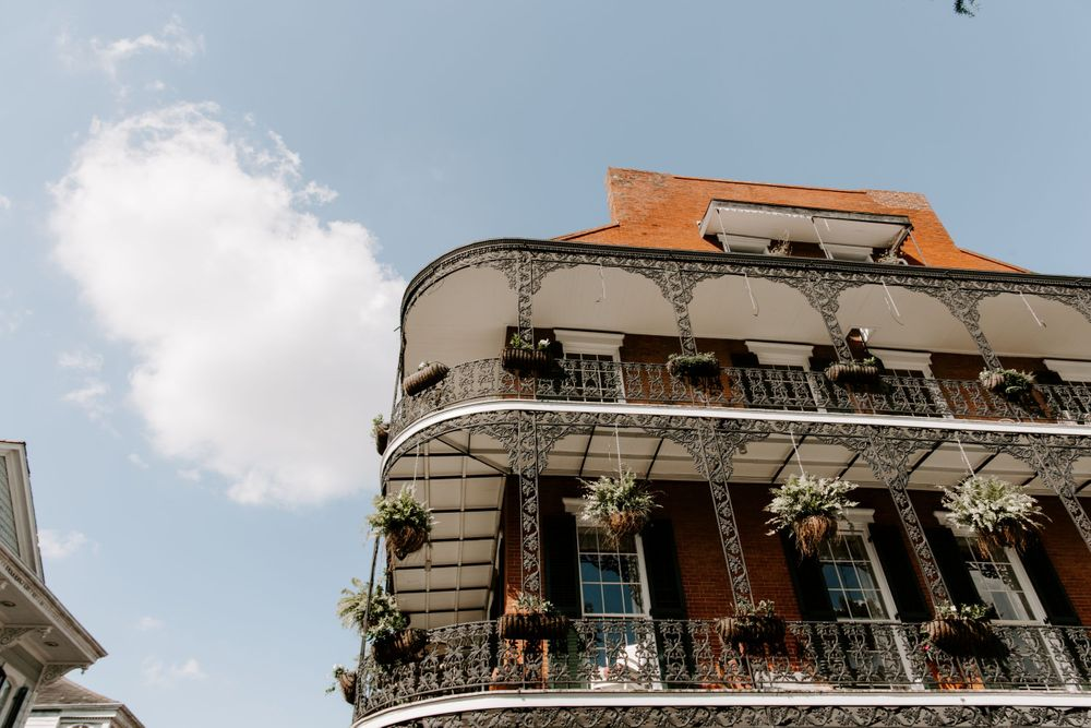 Looking up view of a building in the French Quarter with plants on the balcony,  New Orleans Wedding Photographer