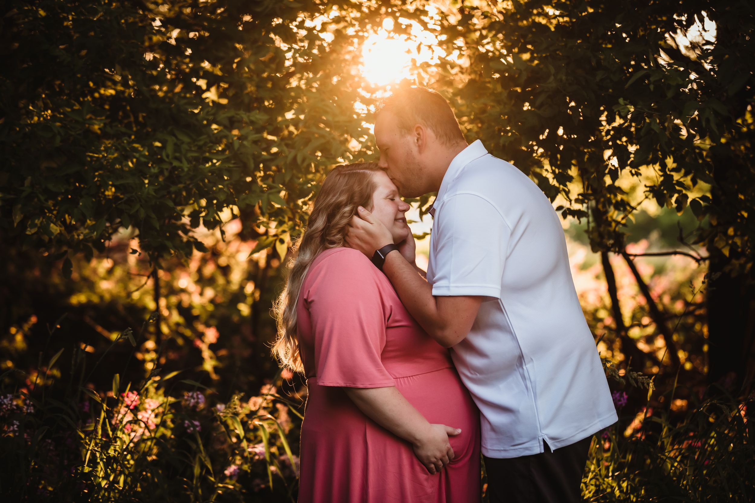 Man grabbing woman's face and kissing her forehead while she holds her pregnant belly.
