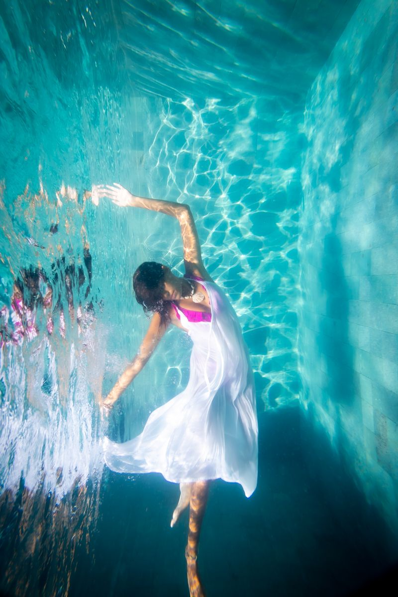 A woman underwater dancing like a ballerina