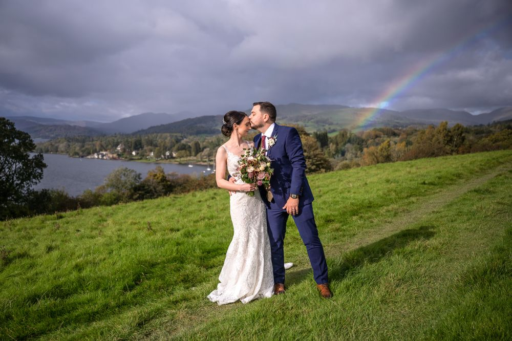 Bride and groom under rainbow at Rayrigg Meadow in Lake District