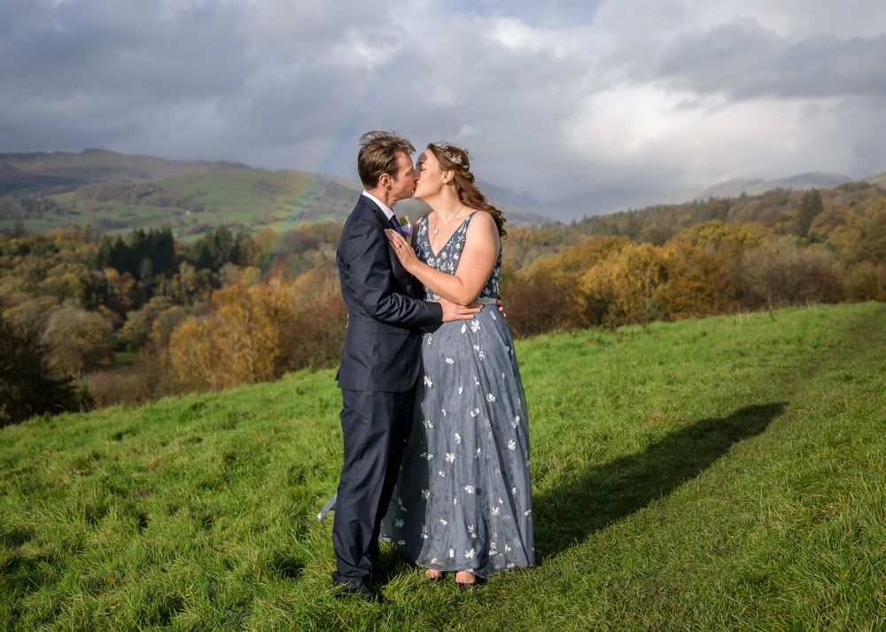 Bride and groom kiss beneath rainbow after a Lake District wedding