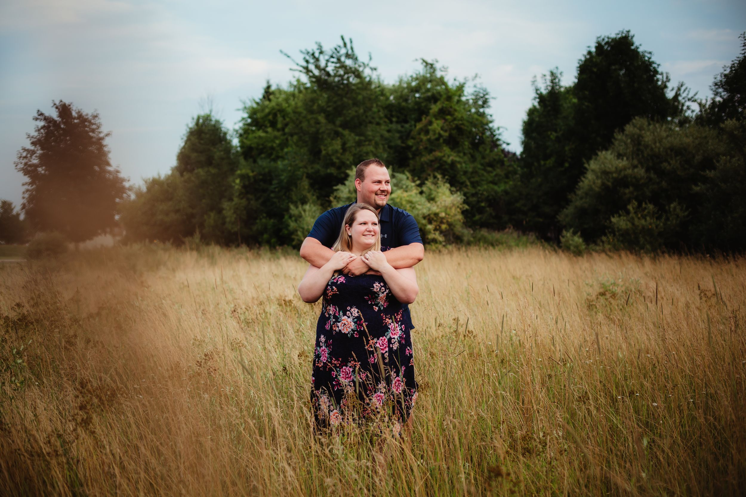 Photo of engaged couple smiling to the right. They are standing in a field with the man hugging woman from behind.
