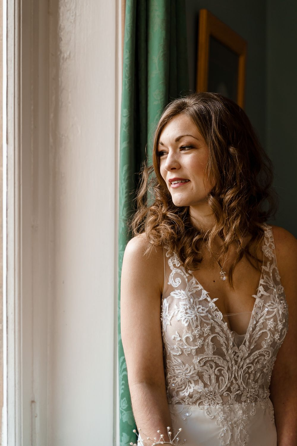 Winchester wedding photography - bride looks whistfully out of the window.