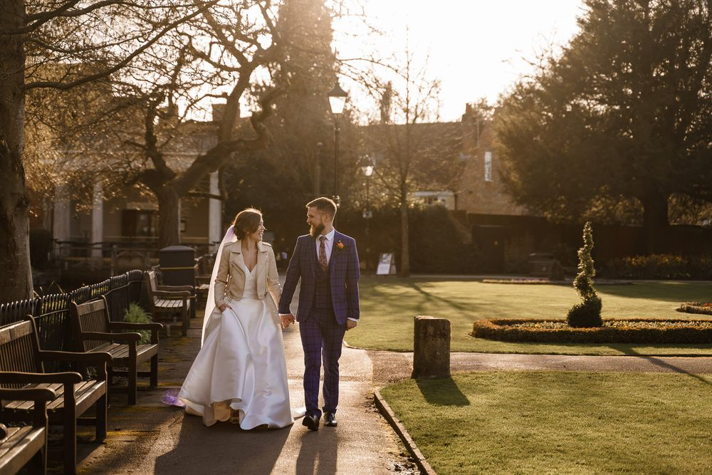 Bride and groom take a walk at golden hour - peacock wedding theme