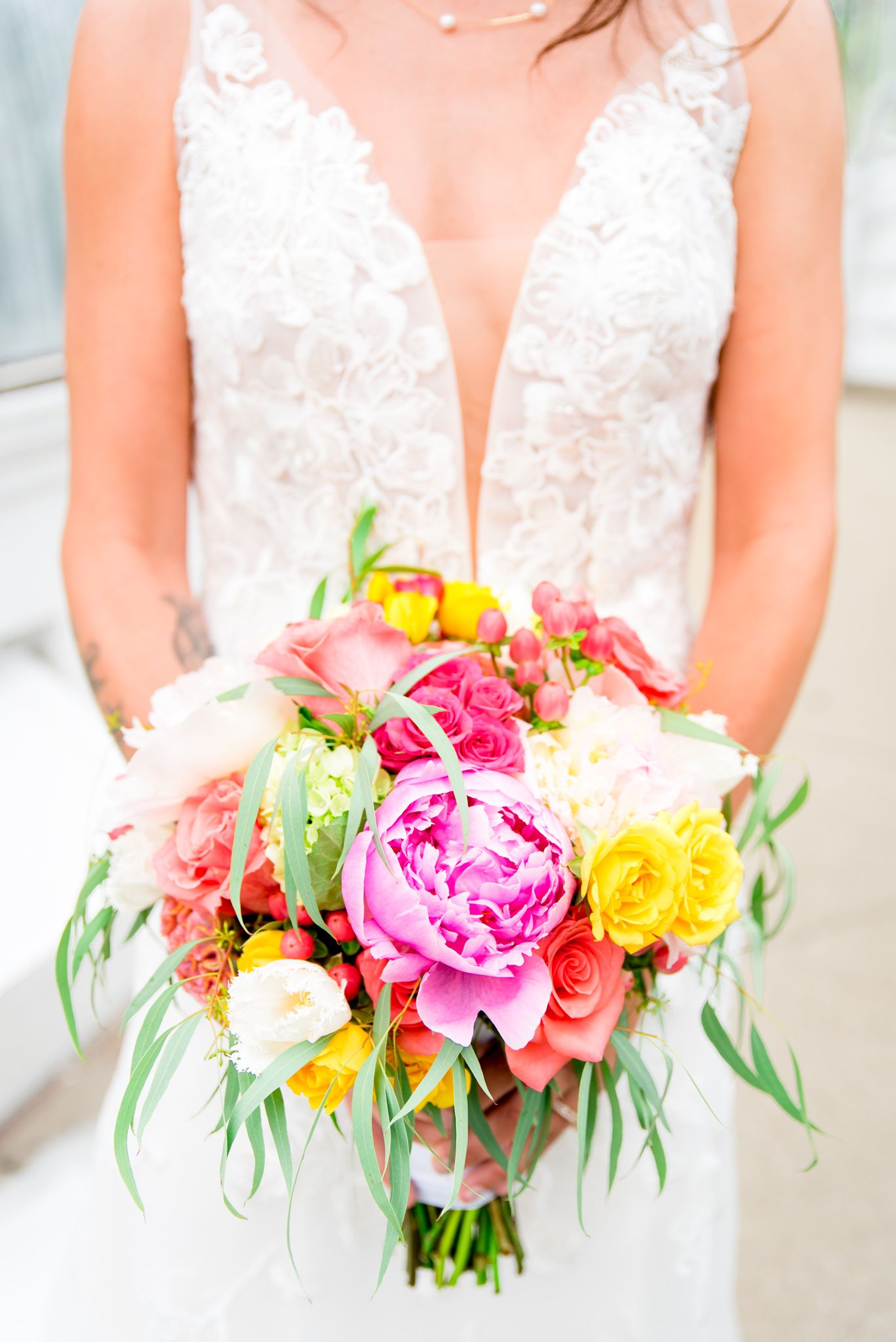 bride in Kelly Faetanini Serafina gown holding a pink, yellow, and green wedding bouquet at Krohn Conservatory