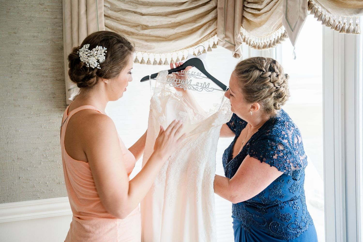 bride and mom taking dress off hanger