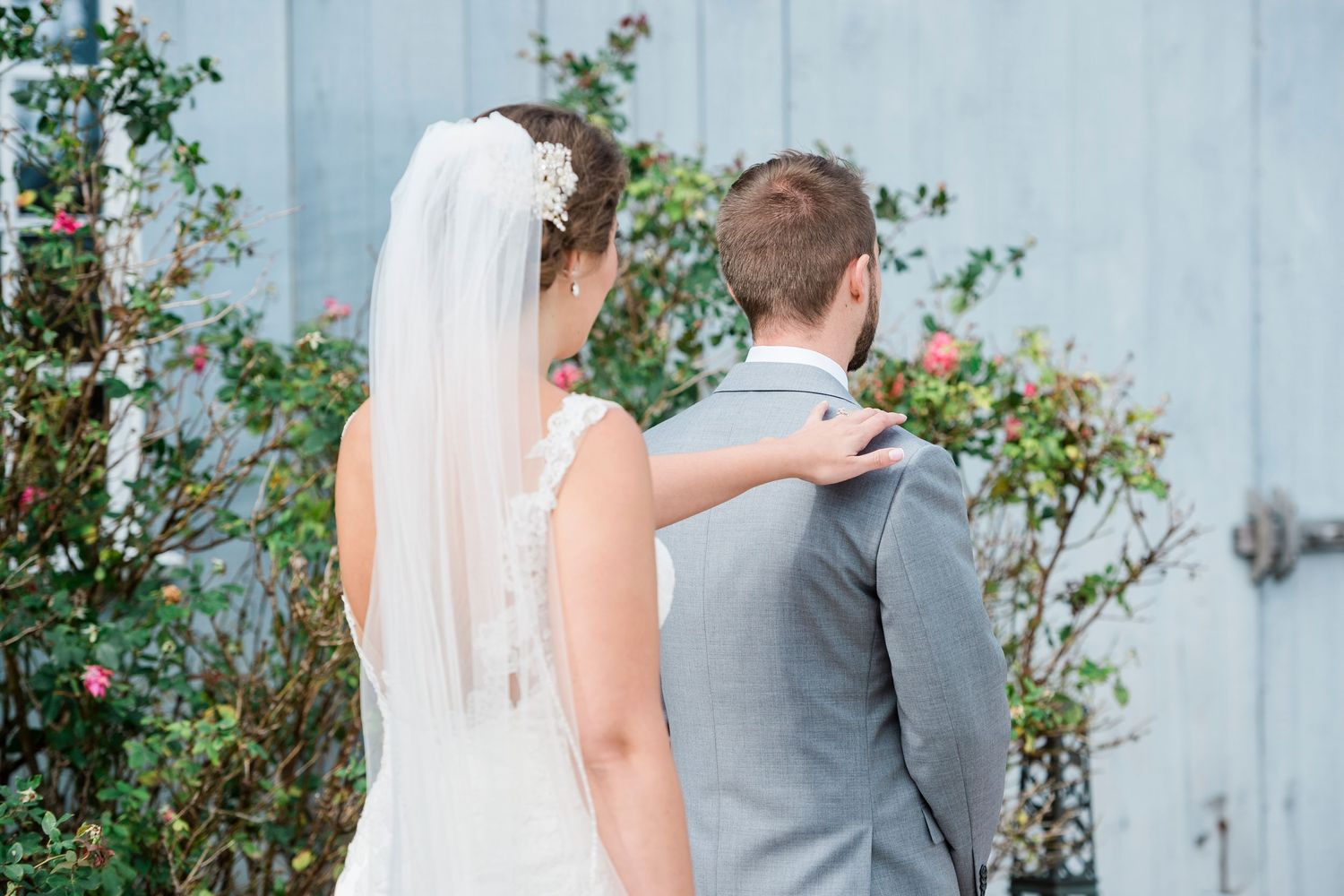 bride taps groom on shoulder during first look