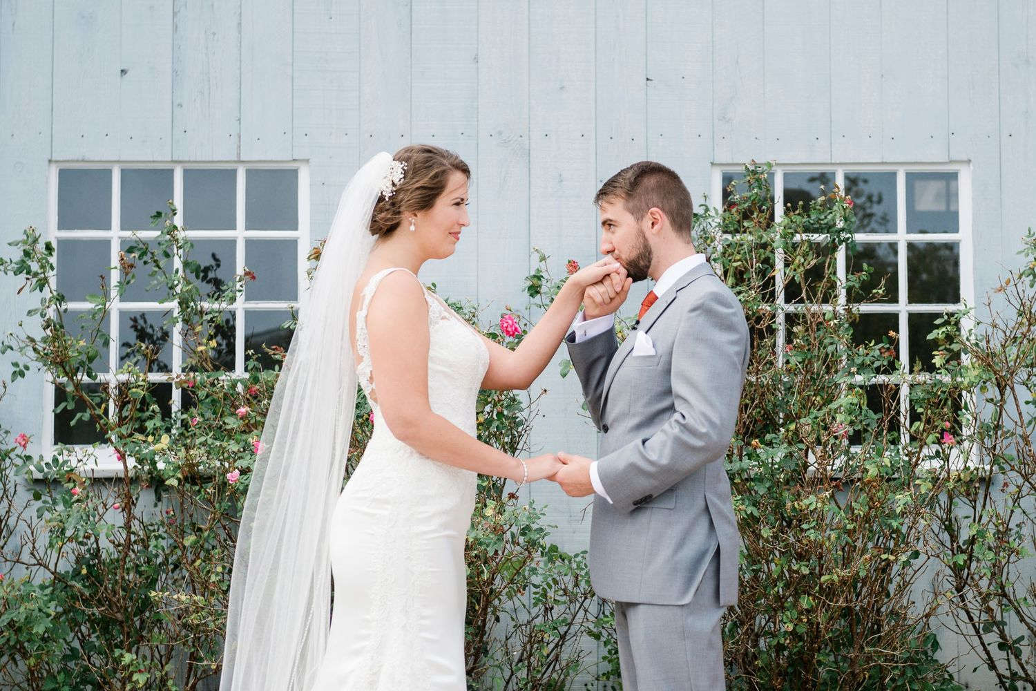 groom holds and kisses brides hand after first look