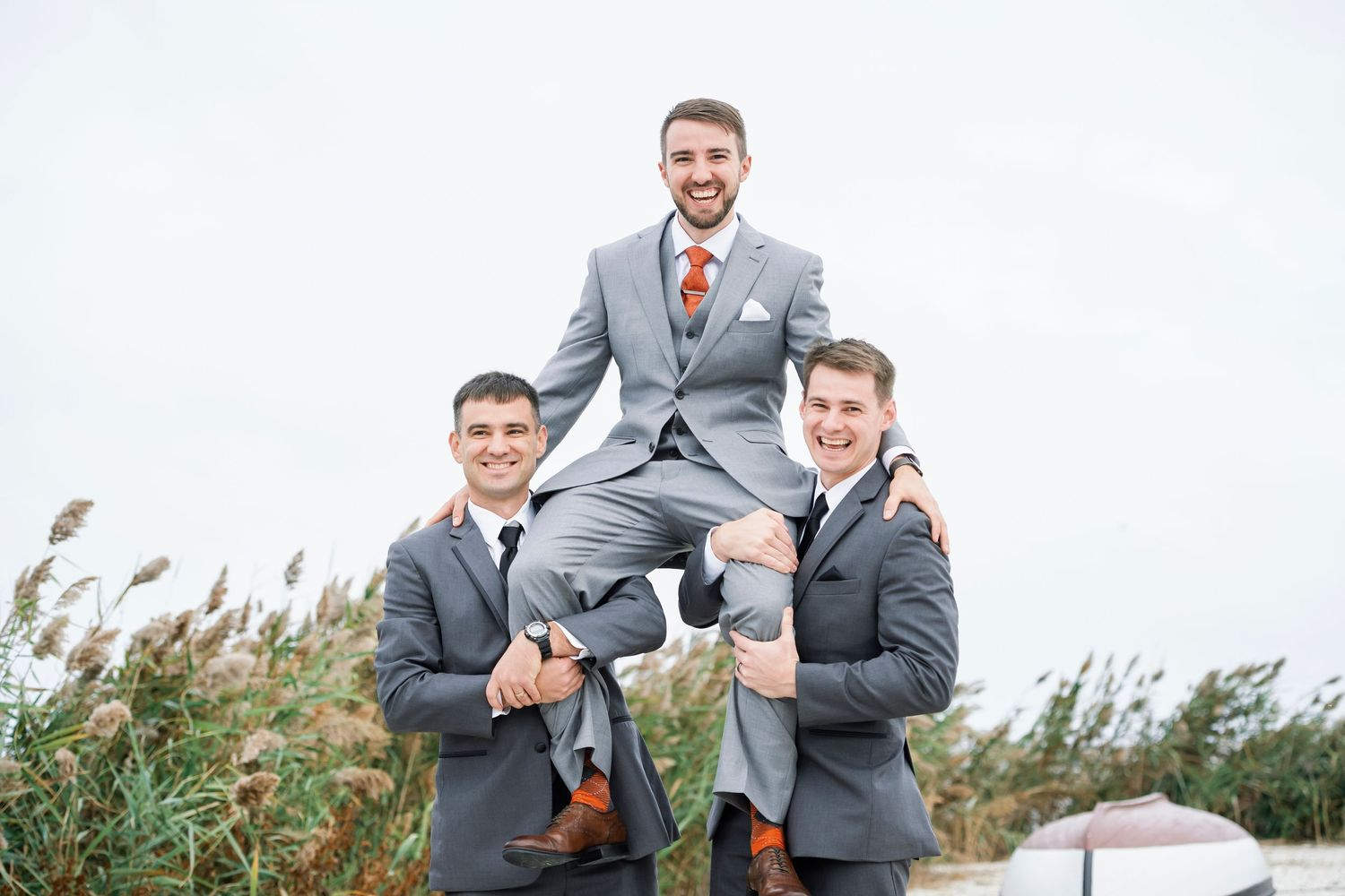 groom's brothers lift him up on their shoulders